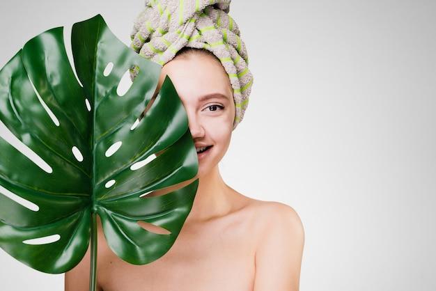 Aantrekkelijk schattig meisje met een handdoek op haar hoofd houdt een groen blad vast en geniet van spabehandelingen