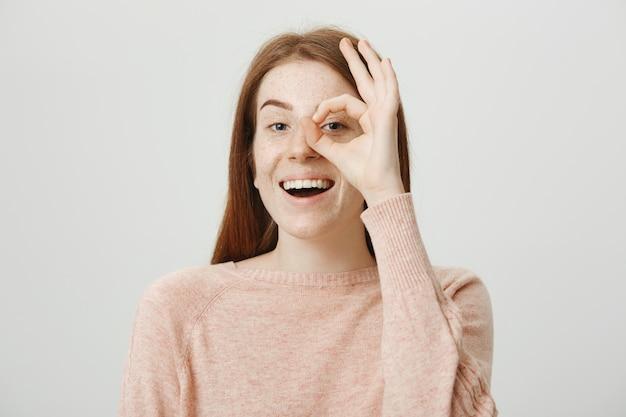 Aantrekkelijk schattig roodharig meisje dat ok gebaar over oog toont, geeft goedkeuring