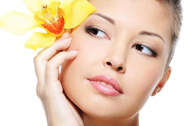 Aantrekkelijk schoonheids aziatisch vrouwelijk gezicht met bloem van oor dat op wit wordt geïsoleerd