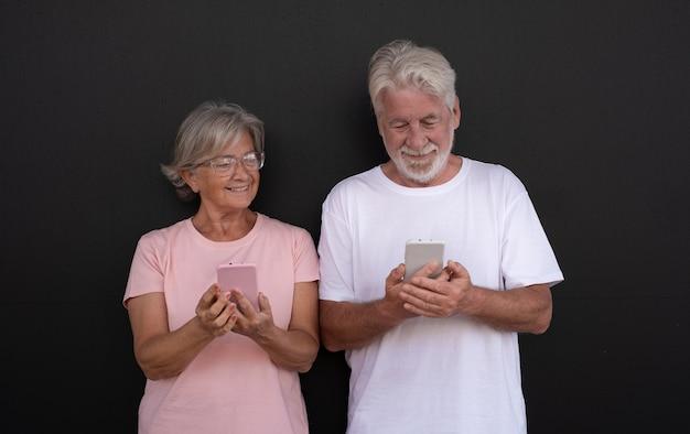 Aantrekkelijk senior koppel glimlachend met behulp van mobiele telefoons oudere gepensioneerde genieten van sociaal en tech