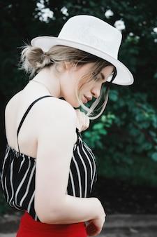 Aantrekkelijk sensueel vrouwelijk model in een gestreepte top en rode vakantiebroek met een hoed in de tuin