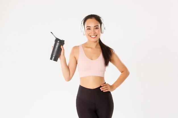 Aantrekkelijk slank en fit aziatisch fitness meisje in koptelefoon, muziek luisteren tijdens training, drinkwater of eiwit uit fles, witte achtergrond.