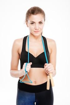 Aantrekkelijk sportmeisje dat touwtjespringen vasthoudt en geïsoleerd op
