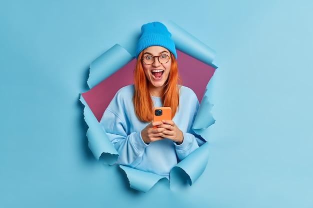 Aantrekkelijk stijlvol roodharig europees meisje krijgt goed nieuws op mobiele telefoon en stuurt sms-berichten gekleed in hoed en casual trui.