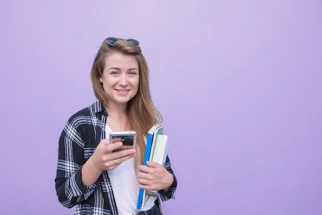 Aantrekkelijk studentenmeisje dat op een purpere achtergrond met boeken, notitieboekjes en een smartphone in haar handen wordt geïsoleerd die de camera en het glimlachen bekijken.