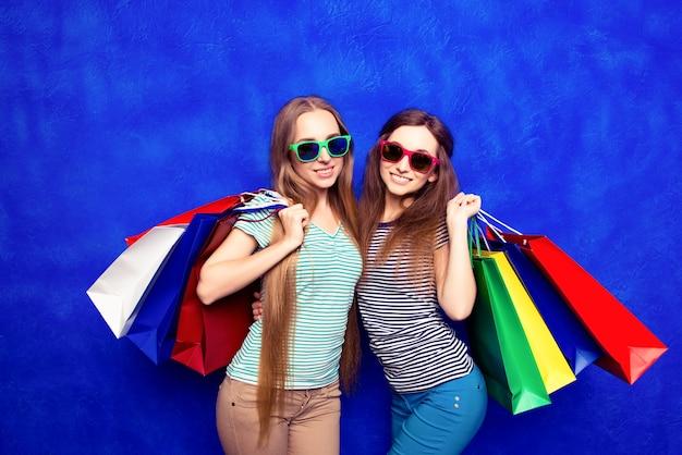 Aantrekkelijk tevreden klanten in glazen met pakjes na het winkelen