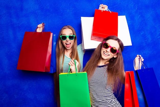 Aantrekkelijk tevreden klanten met pakjes kleding na het winkelen