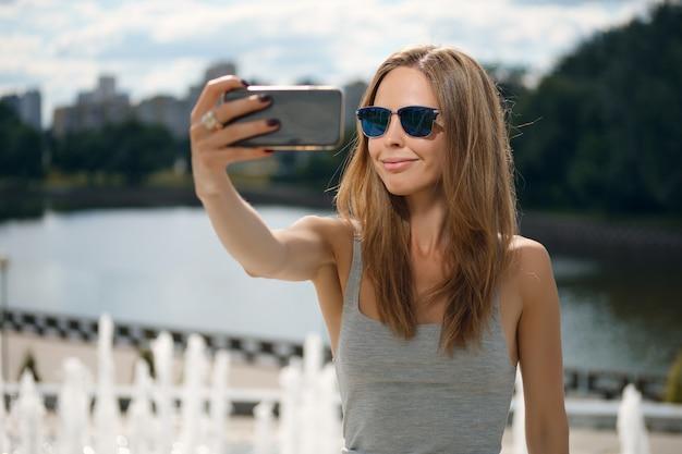 Aantrekkelijk toeristenmeisje die selfie met rivierbank maken op achtergrond in stadspark