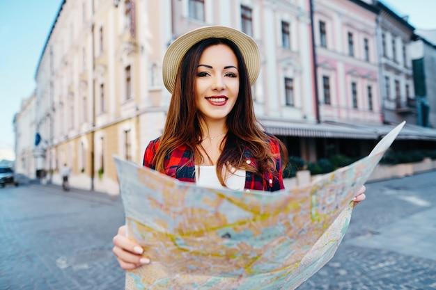 Aantrekkelijk toeristenmeisje met bruin haar dat hoed en rood overhemd draagt, kaart bij oude europese stadsachtergrond houdt en glimlacht, reist.