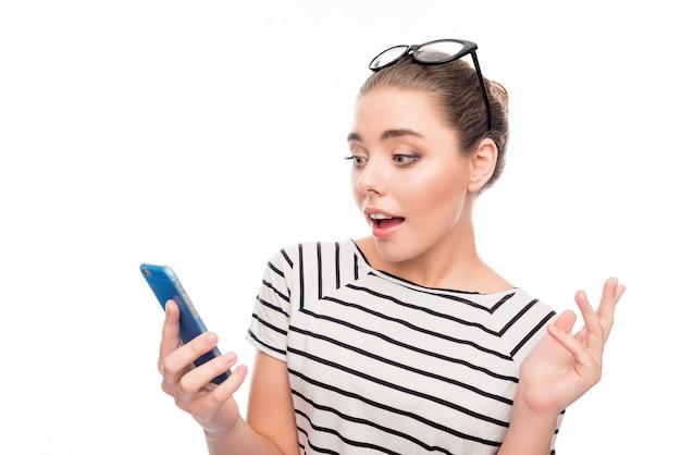 Aantrekkelijk verrast meisje met bril op hoofd met smartphone
