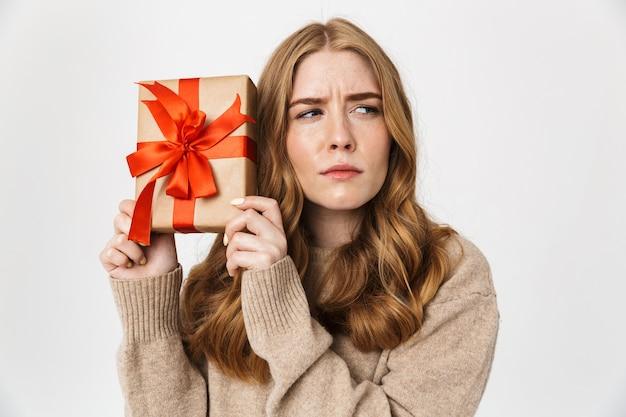 Aantrekkelijk verward jong meisje met een trui die over een witte muur staat en een geschenkdoos toont