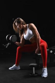 Aantrekkelijk vorm jong sportief geconcentreerd geschiktheidsmeisje met paardestaart die bicepsenoefeningen doen