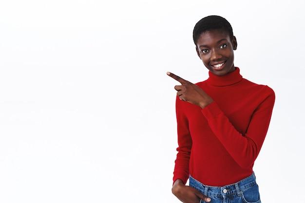 Aantrekkelijk vriendelijk afrikaans-amerikaans vrouwelijk model in rode coltrui geeft advies, wijzende vinger naar links naar lege witte ruimte