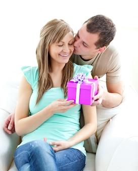 Aantrekkelijk vriendje geeft een cadeautje en een kus aan zijn gloeiende vriendin