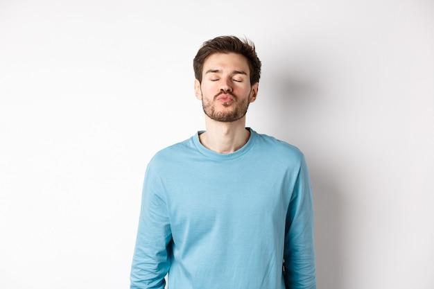 Aantrekkelijk vriendje wachten op kus met gebobbelde lippen en gesloten ogen, permanent in sweatshirt op witte achtergrond.