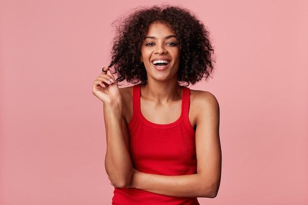 Aantrekkelijk vrolijk afrikaans amerikaans meisje met afro kapsel op zoek deining prachtig speelt met stand van donker krullend haar, lachen, rode singlet dragen, geïsoleerd