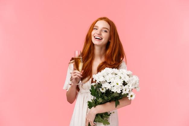 Aantrekkelijk, vrolijk b-day meisje met rood krullend haar, lachend en zorgeloos kijkend naar de camera terwijl ze met vrienden praat tijdens feest, verjaardagsfeest, met boeket witte bloemen en champagneglas.
