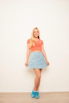 Aantrekkelijk vrolijk jong model dat haar blauwe rok toont