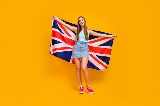 Aantrekkelijk vrolijk meisje dat grote britse vlag houdt die over gele kleurenachtergrond wordt geïsoleerd