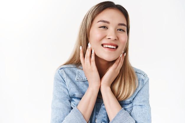 Aantrekkelijk vrolijk teder jong aziatisch blond meisje, zorg voor de huid, aanraking, gezicht, opgetogen, voel zachte, zachte wangen, breed glimlachen, geniet van cosmeticaproduct