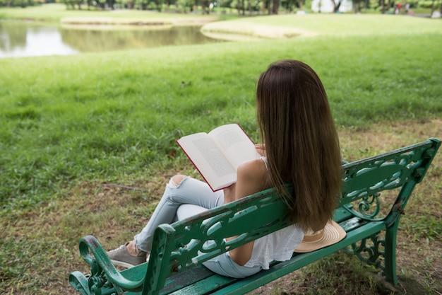 Aantrekkelijk vrouw gelezen boek in park