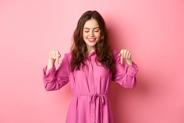 Aantrekkelijk vrouwelijk model in lente-outfit, wijzend en neerkijkend, met copyspace opzij, staande tegen roze muur.