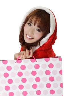 Aantrekkelijk winkelend meisje in kerstkleren die lachend gezicht tonen.