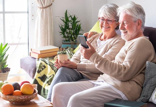 Aantrekkelijk witharig senior koppel dat thuis op de bank ontspant en samen naar smartphone kijkt in een videogesprek met familie of vrienden. glimlachende senioren die genieten van draadloze technologie