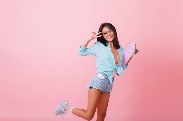 Aantrekkelijk zwartharige vrouwelijk model in casual zomerkleding dansen. verfijnd spaans meisje in sportieve schoenen die op één been stellen en glimlachen.