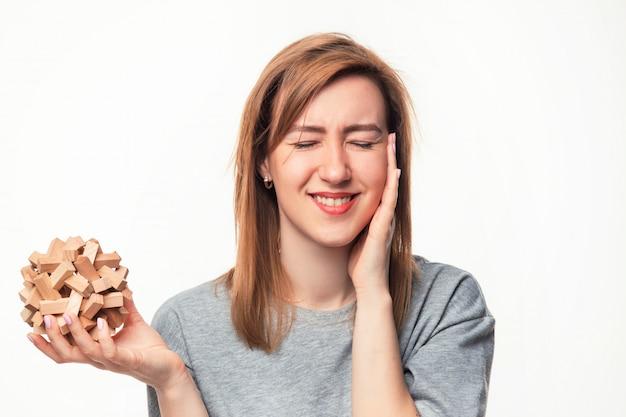 Aantrekkelijke 24-jarige zakenvrouw op zoek verward met houten puzzel.