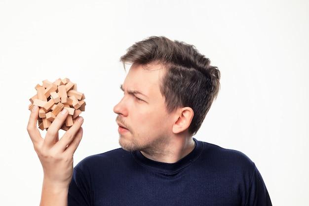 Aantrekkelijke 25-jarige zakenman kijkt verward op houten puzzel.