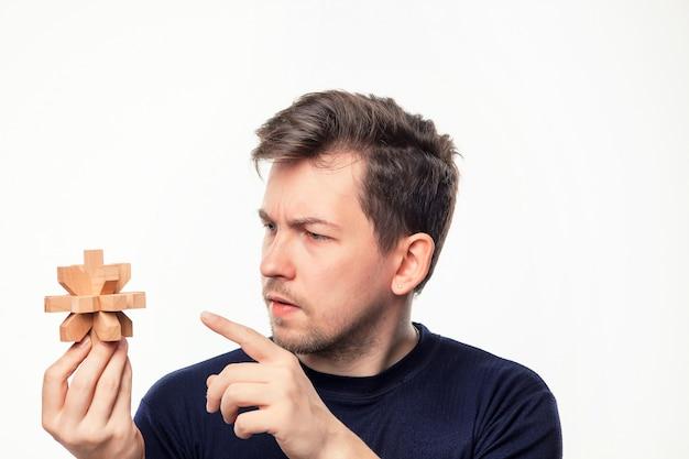 Aantrekkelijke 25-jarige zakenman op zoek verward houten puzzel.