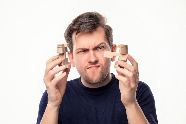 Aantrekkelijke 25-jarige zakenman op zoek verward met houten puzzel.