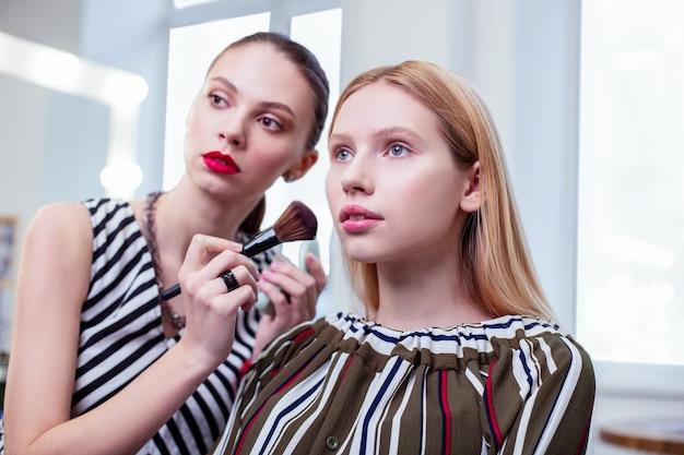 Aantrekkelijke aangename vrouw die aan haar uiterlijk denkt tijdens een bezoek aan een schoonheidssalon Premium Foto