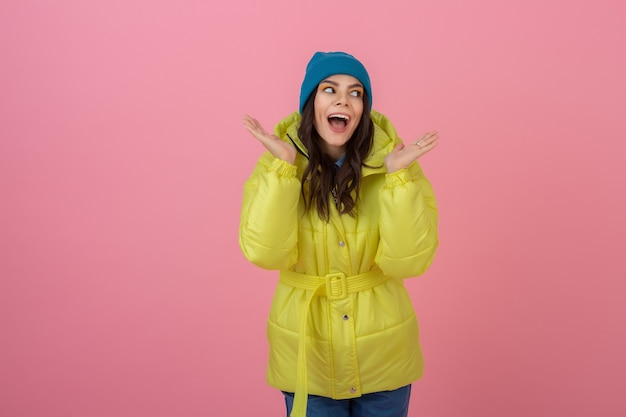 Aantrekkelijke actieve vrouw die zich voordeed op roze muur in kleurrijke winter donsjack van felle gele kleur, glimlachend plezier, warme vacht modetrend, gek geschokt verrast gezicht expressie