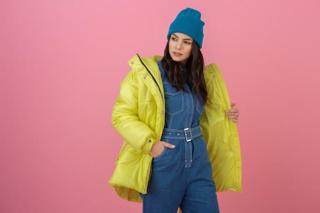 Aantrekkelijke actieve vrouw model poseren op roze muur in kleurrijke winter donsjack van heldere gele kleur, warme vacht modetrend