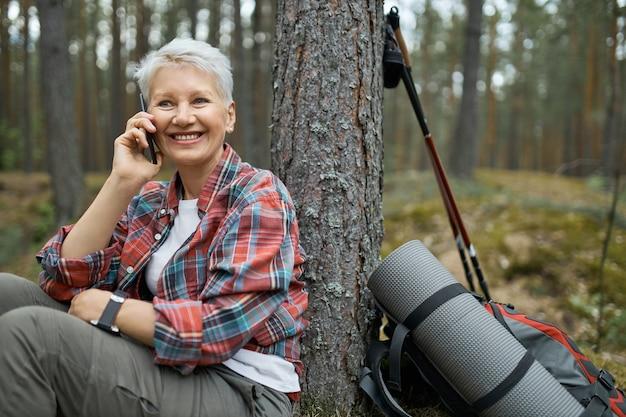 Aantrekkelijke actieve vrouwelijke gepensioneerde m / v in geruite overhemd met kleine pauze tijdens het wandelen in het bos, zittend onder de boom, praten met vriend op mobiel. vrouw van middelbare leeftijd reiziger telefoneren