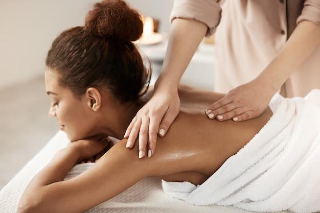 Aantrekkelijke afrikaanse vrouw die massage het ontspannen in kuuroordsalon heeft. gesloten ogen.