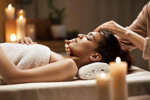 Aantrekkelijke afrikaanse vrouw genieten van gezichtsmassage in spa salon.