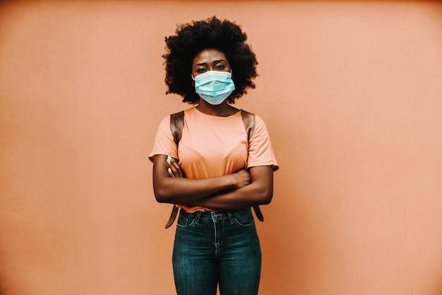 Aantrekkelijke afrikaanse vrouw met gekruiste armen en masker op haar gezicht. covid19-uitbraak.