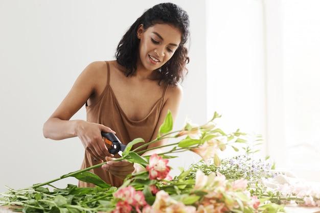 Aantrekkelijke afrikaanse vrouwelijke bloemist die scherpe stammen glimlachen die in bloemwinkel werken over witte muur.