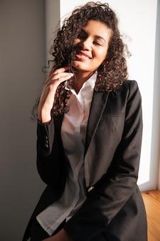 Aantrekkelijke afrikaanse zakenvrouw in de buurt van venster. ogen dicht.