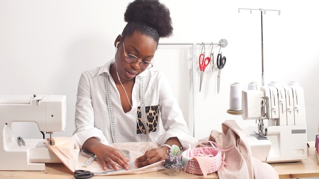 Aantrekkelijke afro-amerikaanse vrouwelijke modeontwerper naait modieuze kleding in haar atelier