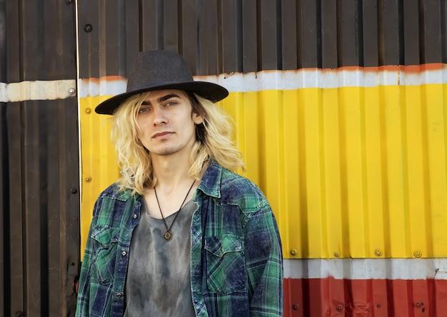 Aantrekkelijke armeense man met een hoed die naar de camera kijkt op een gele, zwarte en rode muur