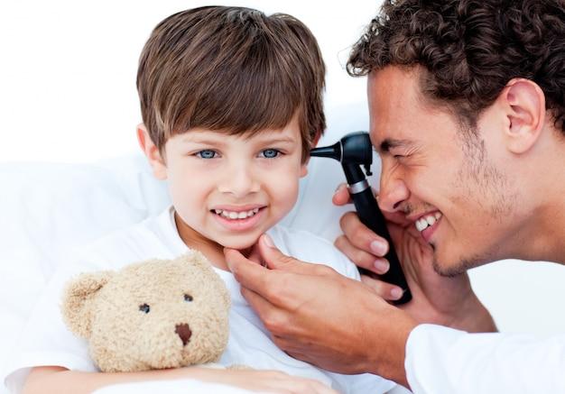 Aantrekkelijke arts die de oren van de patiënt onderzoekt