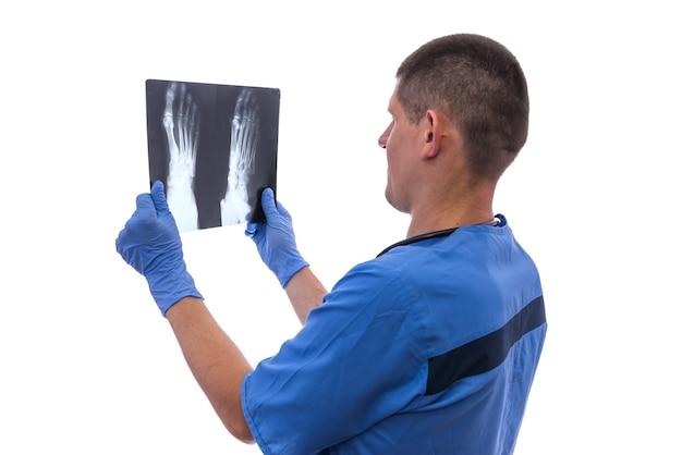 Aantrekkelijke arts die een voetröntgenstraal houdt. röntgenfoto onderzoeken.
