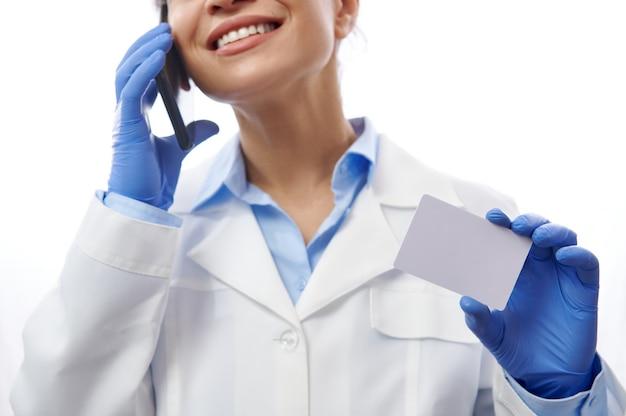 Aantrekkelijke arts met mooie glimlach praat op mobiele telefoon en toont plastic kaart op camera op witte achtergrond met kopie ruimte. detailopname. ziektekostenverzekering concept