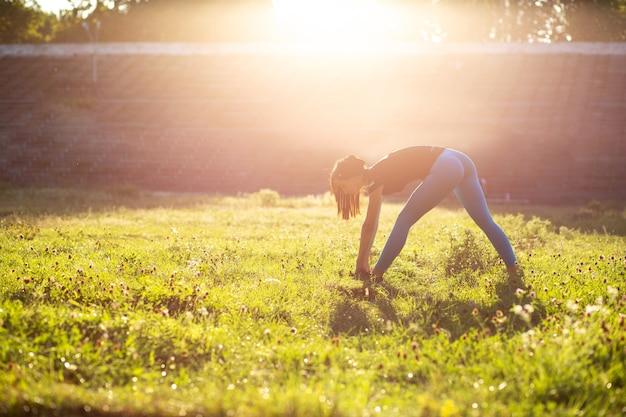 Aantrekkelijke atletische vrouw die zich uitstrekt voor de training in het stadion. buiten geschoten met zonnestralen. ruimte voor tekst