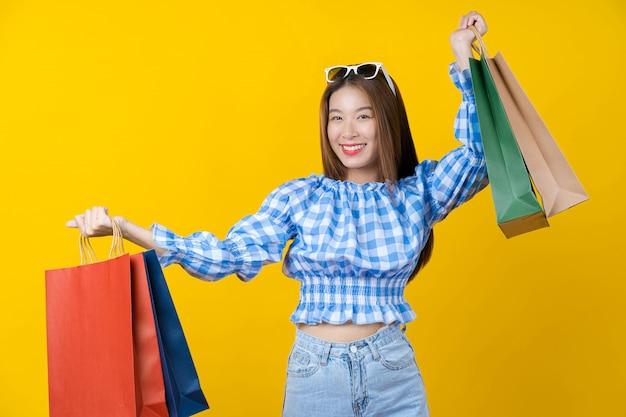 Aantrekkelijke aziatische glimlachende jonge vrouw dragende het winkelen kleurenzak op geïsoleerde gele kleurenmuur