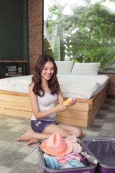 Aantrekkelijke aziatische jonge vrouw die een reistas inpakt voordat ze op vakantie gaat. levensstijlconcept.